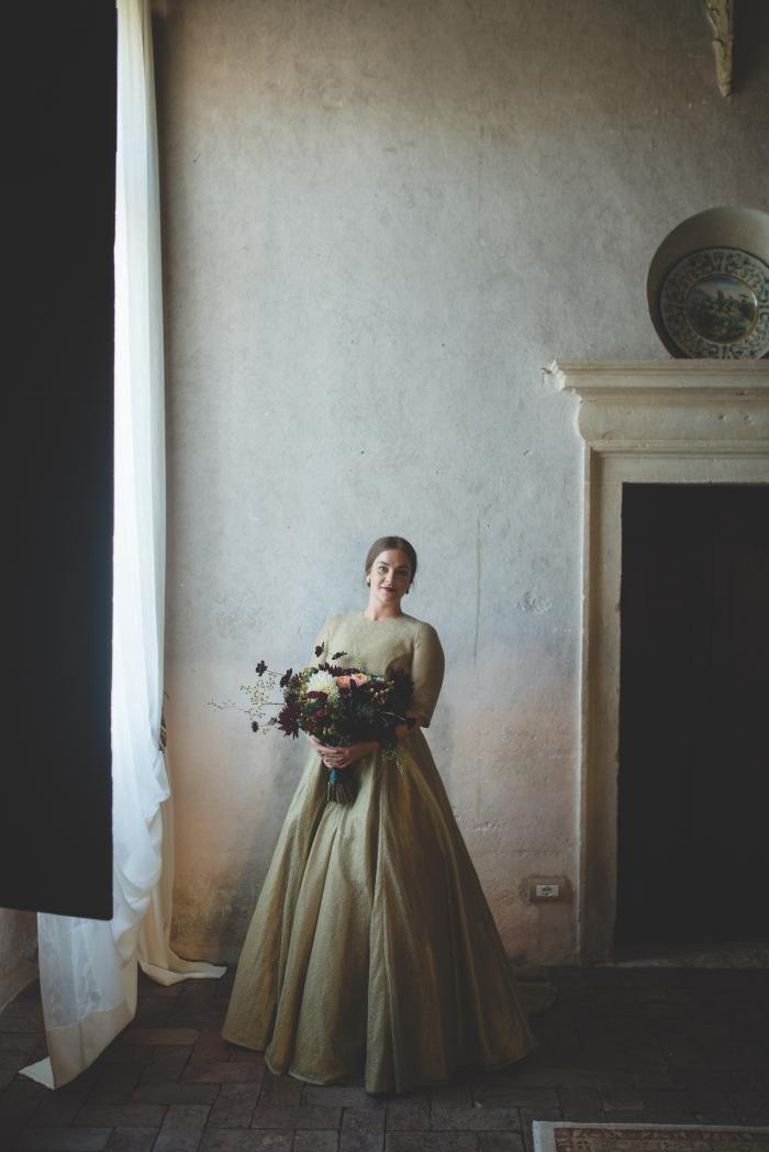 Paula's dress, full length with bouquet, stone wall fireplace